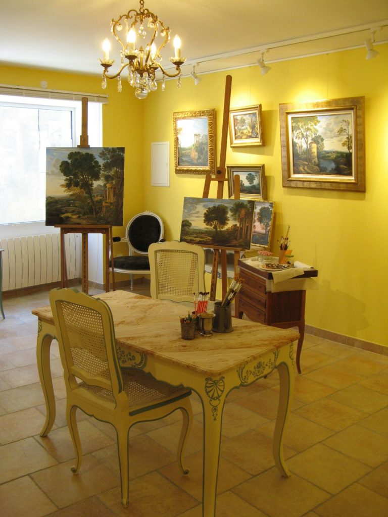 Looking across the gallery to the window, with paintings on the brightly painted yellow walls