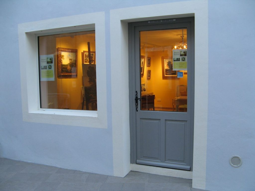 A grey door leading into the gallery at 25 rue des Tourterelles in Lapradelle-Puilarens